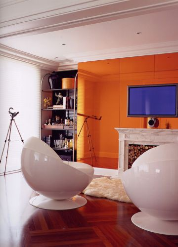 Na sala de TV, o vão deixado entre a parede e a janela foi ocupado com uma estante/bar