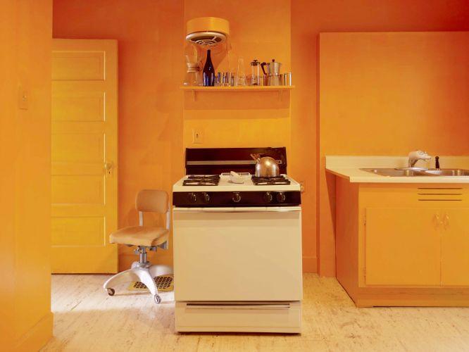 A cozinha da casa de Raveevarn Choksombatchai, em São Francisco, Califórnia, é espartanamente mobiliada. O destaque do ambiente fica por conta da tinta laranja aplicada nas paredes e no teto