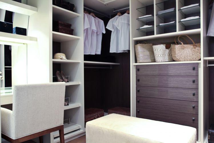 Projetado por Débora Aguiar, esse closet com armários sem portas tem bastante espaço para cabides, um grande gaveteiro e prateleiras (algumas de vidro, que são fáceis de limpar e permitem a passagem de luz). O espaço tem, também, uma bancada com espelho e uma poltrona