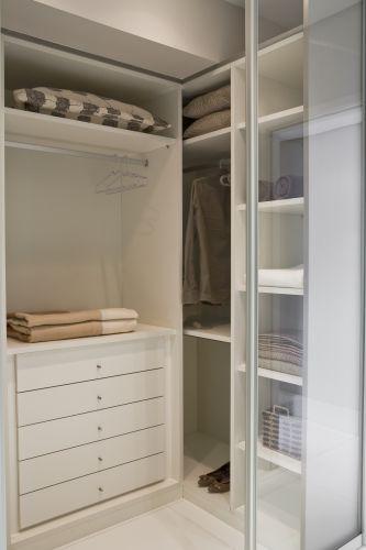Closet da Elgin Móbili Design com acabamento branco de toque aveludado. As gavetas com corrediças têm sistema que não permite que elas saiam do trilho. Uma porta de correr com vidro translúcido separa o cômodo do dormitório