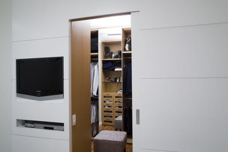 O Studio Costa Marques projetou este closet. Ele é separado do quarto por um painel (que abriga a TV) e acessado por uma porta de correr, ambos de madeira freijó linheiro com acabamento de laca branca