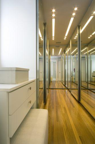 O closet estreito parece maior devido à quantidade de espelhos que revestem as portas dos armários da Ornare. O projeto é da arquiteta e decoradora Sueli Adorni. Sueli instalou um pequeno móvel auxiliar com gavetas, que abriga um pufe (da Ornare)