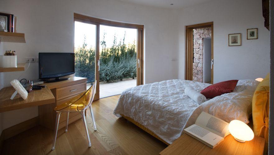 Em um dos quartos da casa na Sardenha (Itália), de Cossu & Tedesco Arquitetos, cama com cabeceira estofada em sarja, marca Ikea. Cadeira Mr. Impossibile, em acrílico, do Phillipe Starck, Kartell. Assoalho em madeira de carvalho e esquadrias idem