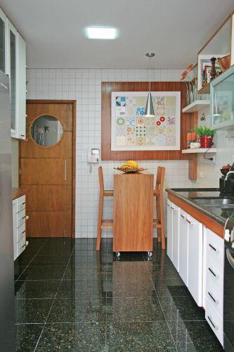 Na cozinha, o projeto manteve o piso de granito e o revestimento cerâmico da parede, rebaixando o teto com forro de gesso para embutir a iluminação