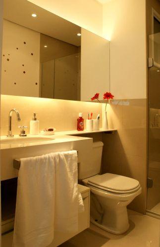 No banheiro, os destaques ficam por conta da cuba embutida na bancada e na iluminação atrás do espelho, embutida em uma caixa de gesso. O toalheiro também foi disposto de forma a ganhar espaço