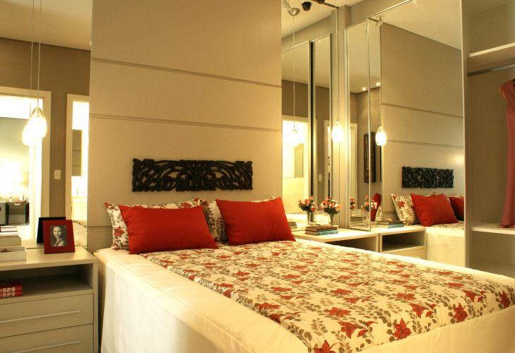 No quarto de casal, o espelho na parede e na porta do armário amplia e multiplica a luz natural. Sobre a cama da Tok&Stok, o painel em MDF faz o papel de cabeceira