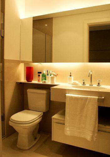 No banheiro, os destaques ficam por conta da cuba embutida na bancada e na iluminação atrás do espelho, embutida na caixa de gesso. O toalheiro também foi disposto de forma a ganhar espaço