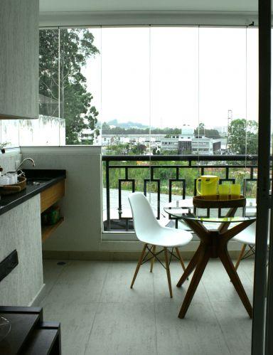 A varanda dotada de pia e churrasqueira comporta mesa para refeições