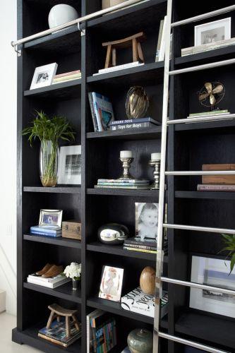 Na parede branca de pé-direito duplo destaca-se a estante de madeira escura projetada pelo arquiteto Dado Castello Branco. Os objetos são do Depósito São Martinho, da LS e do acervo pessoal dos proprietários