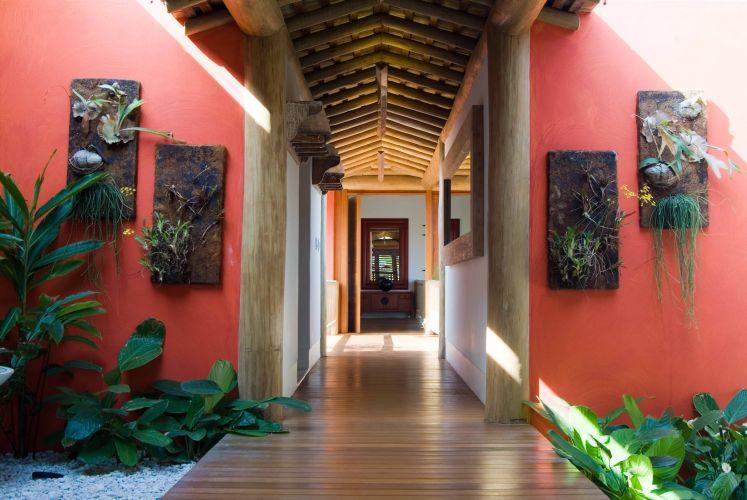 Vista da passarela de ligação entre o bloco social e o íntimo da casa. A cor vermelha e o paisagismo conferem calor e o clima despojado da obra