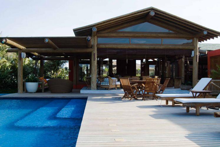 O deck de cumaru tratado com cera carnaúba fosca dá a sensação visual de estar flutuando sobre a piscina. O emprego de várias madeiras se destaca na casa