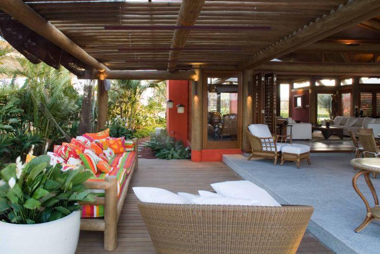 O ambiente de estar é totalmente integrado à varanda sob o pergolado de ripas de madeira, um agradável espaço de convívio com móveis rústicos e estofados forrados com tecidos coloridos