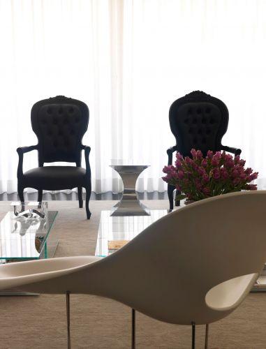 Em primeiro plano, a La Chaise, de Charles e Ray Eames, escolhida para ficar na entrada da casa. A peça oferece, em qualquer ângulo, uma visão agradável ao observador