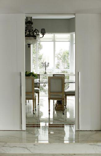 Grandes portas de correr brancas isolam a sala de jantar. O vão em que elas foram instaladas foi aumentado, ficando mais alto. O mármore que reveste o piso é do projeto original do apartamento e foi recuperado