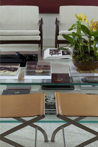 Harmonia e simetria marcam esta composição do estar, com duas banquetas de couro caramelo, da Casual, em frente a duas poltronas dinamarquesas revestidas com veludo claro, da Etel. A mesa central de vidro, com livros e objetos, garante leveza ao ambiente