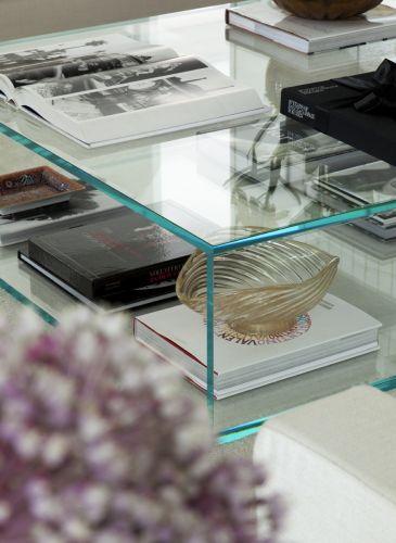 Mesa de centro de vidro executada pela Vidroart com livros e objetos decorativos, como o bowl de Murano, de Teo Antiquário