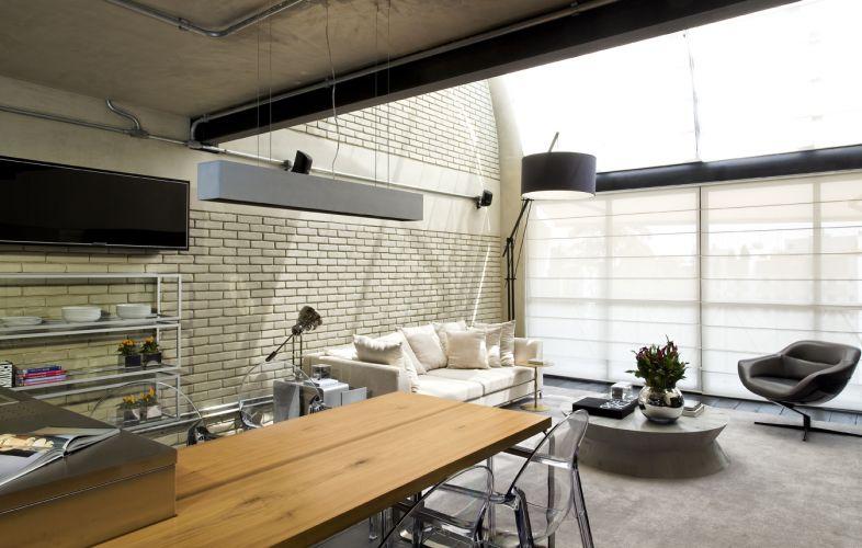 As paredes do loft reformado pelo arquiteto Diego Revollo receberam uma camada fluida de cimento queimado, preservando, assim, os tijolos aparentes. A grande área envidraçada é coberta por uma tela solar de acionamento eletrônico