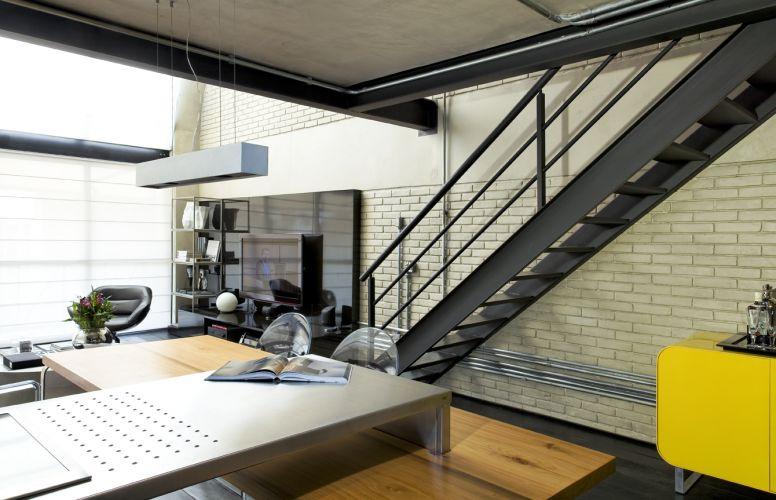 A escada metálica teve as pisadas revestidas com a mesma madeira que forma o piso do pavimento térreo do loft. Sob ela, um aparador laqueado de amarelo serve como bar. A peça foi desenhada pelo arquiteto Diego Revollo