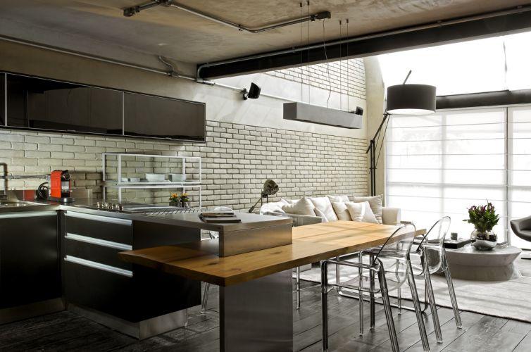 A bancada que divide o estar e a cozinha do loft serve de apoio para pia e fogão. Ela é de aço e foi executada pela Mekal. Ligada à base de inox, está o tampo de madeira que forma a mesa de jantar. O piso de madeira ebanizada é o mesmo em todo o pavimento térreo do loft