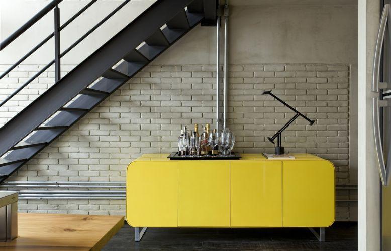 O aparador de madeira laqueada de amarelo brilhante foi desenhado por Diego Revollo. A peça funciona como bar e demarca a entrada do apartamento (a porta principal está à direita do móvel). As portas guardam copos, bebidas e utensílios de bar