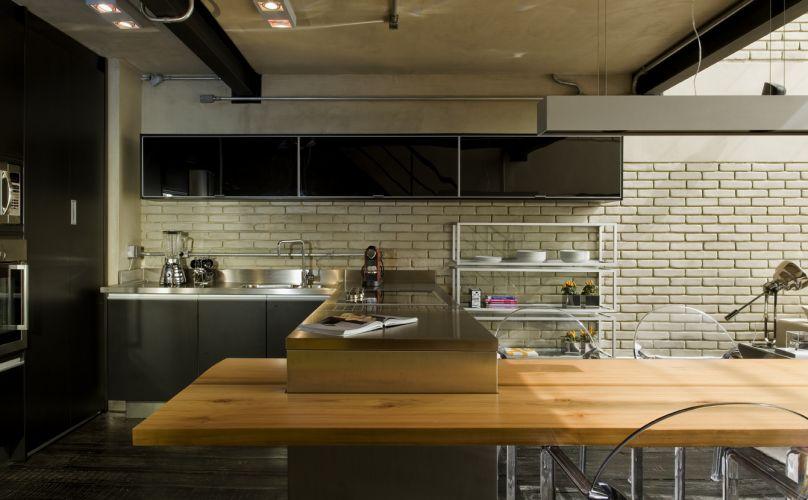 A bancada que divide o estar e a cozinha do loft serve de apoio para pia e fogão. Ela é de aço e foi executada pela Mekal. Ligada à base de inox está o tampo de madeira que forma a mesa de jantar. Ao fundo, armário suspenso de vidro executado pela Florence