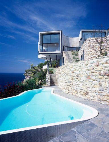 Piscina com borda infinita e muros de pedra de um dos terraços escalonados da casa Holman, na Australia, de Durbach Block Jaggers Architects. Uma parte da área social projeta-se para o mar, sustentada por pilotis