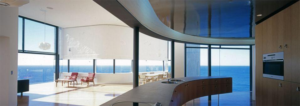 Cozinha contemporânea na área social da casa Holman, obra de Durbach Block Jaggers Architects localizada em um subúrbio de Sydney. O ambiente integrada as salas de estar e jantar e tem vista para o mar. As paredes brancas e o piso de madeira fazem contraponto aos pilares e esquadrias metálicos pretos