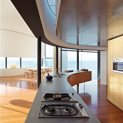Cozinha contemporânea na área social da casa na Australia, integrada às salas de estar e jantar, e com vista para o mar. As paredes brancas e o piso de madeira fazem contraponto aos pilares e esquadrias metálicos pretos