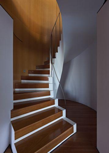 Escada em curva que liga internamente os dois pavimentos da casa Holman, em Sydney, obra de Durbach Block Jaggers Architects. Os piso e espelhos de madeira da escada incrustam-se na alvenaria e integram-se perfeitamente ao revestimento da parede e do piso