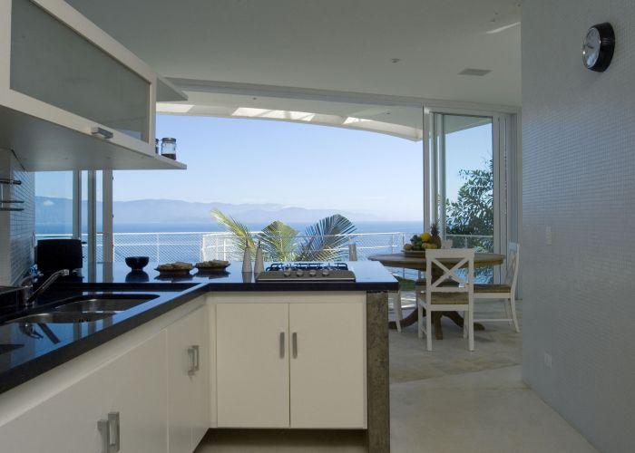 Também da cozinha é possível apreciar a vista do mar. O ambiente tem as paredes revestidas de pastilhas brancas e armários embutidos em um balcão de concreto com tampo de pedra negra. Projeto do arquiteto Enrico Benedetti