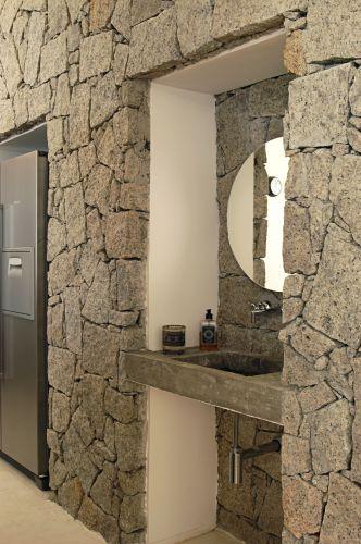 Na parede revestida de pedra foram previstos dois nichos: um abriga para a geladeira e, o outro, um lavabo. Casa no litoral paulista projetada pelo arquiteto Enrico Benedetti