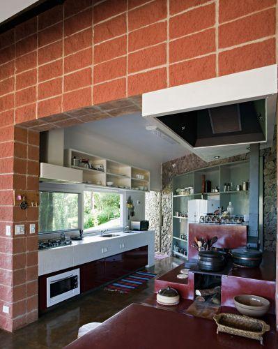 A cozinha, compacta, liga-se ao estar por meio do fogão mineiro, movido a lenha, que além da cocção dos alimentos, ele também serve para manter os ambientes sociais mais aquecidos. Para evitar que a fumaça invada os ambientes, há uma coifa embutida na marcenaria. Do lado oposto, na bancada, o cook-top, acompanhado de forno, ambos da Bosch