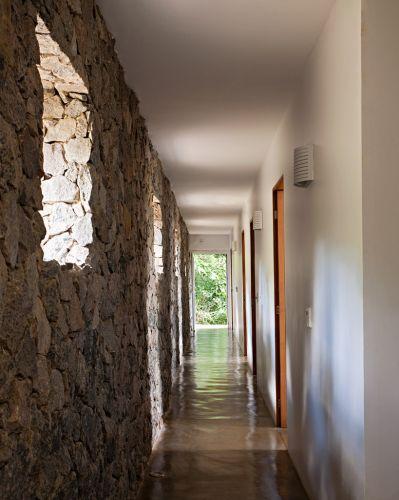 O muro em pedra rachão conduz o corredor de distribuição. Para garantir luz natural, aberturas estratégicas