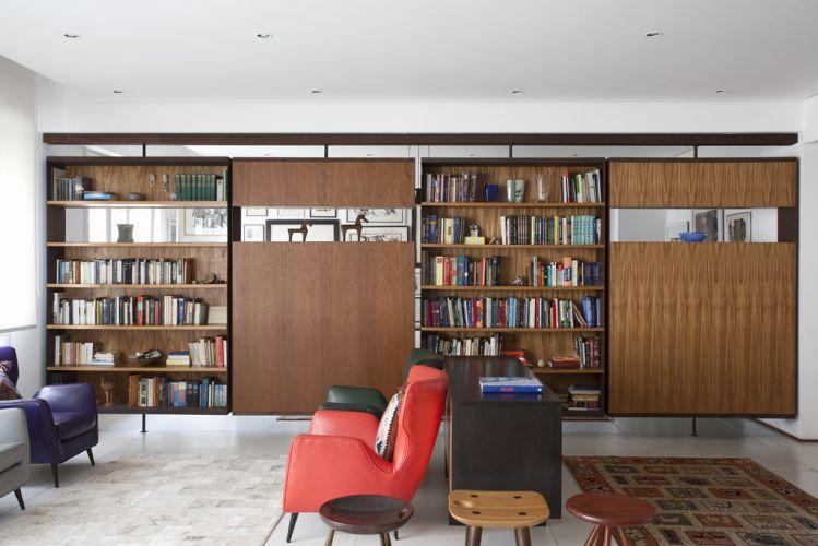 As estantes pivotantes têm estrutura de aço corten e são revestidas de freijó; elas separam o estar do escritório, garantindo mais privacidade ao ambiente