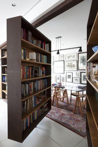 Vista do escritório por entre as estantes pivotantes. O colorido vem dos elementos de decoração, como o tapete e dos livros. A luminária pendente sobre a mesa de trabalho é da Reka