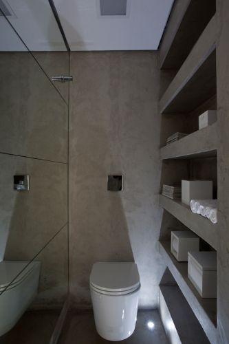 Premiado, este lavabo destaca-se pelo aproveitamento do espaço. Nichos moldados em concreto entre a coluna e a parede abrigam papel, toalhas, revistas, perfumes e outros acessórios. Repare na iluminação que vem de baixo: ela ressalta a volumetria do vaso sanitário, da linha Link da Deca, e dá mais intimidade ao local
