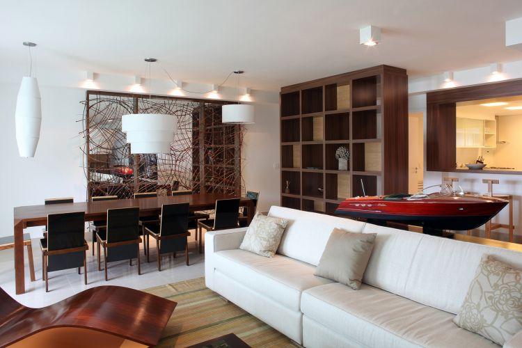 A sala de jantar está ligada diretamente ao living e ao bar. Com paredes, teto e piso claros, tem mobiliário em tonalidades mais escuras de marrom. Os móveis foram usados para modificar espacialmente o apartamento, visto que uma reforma foi vetada pelos proprietários