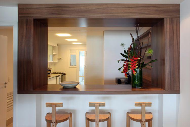 O bar, antes com tampo e molduras de granito, foi revestido com folhas de madeira. A intervenção fez com que o ambiente se integrasse às áreas sociais, desligando-se da cozinha. Os bancos Girafa, desenhado por Lina Bo Bardi, foram feitos pela Marcenaria Baraúna