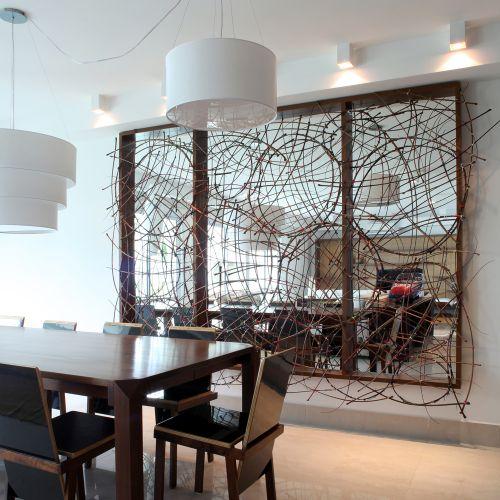 A mesa e as cadeiras de jantar são da Marcenaria Baraúna. As últimas têm estrutura de madeira maciça e planos de assento e encosto de compensado naval revestido de laminado melamínico. Sobre o espelho amplo, escultura de gravetos com design de Frederico Zanelato e execução do artista plástico Maurício Chaer