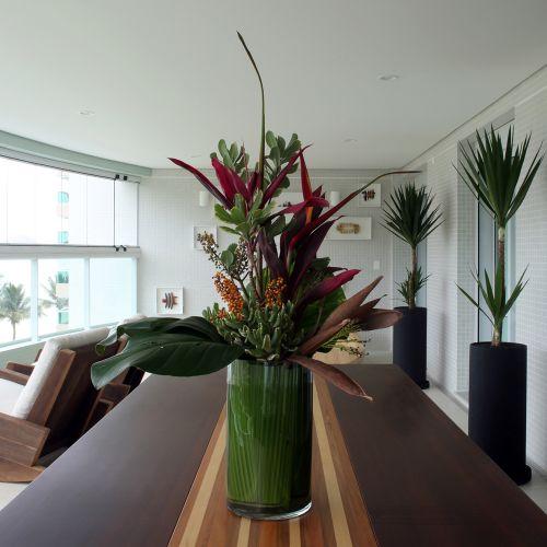 Sobre a mesa de marchetaria, o arranjo floral do paisagista Fernando Yamasaki dá cor à varanda bem arejada