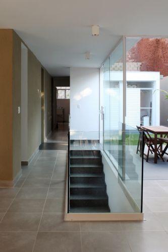Foto mostra a escada que dá acesso ao pavimento que comporta todos os cômodos íntimos e sociais da casa SALC. A solução para o terreno em aclive foi o nivelamento via pilotis e o aproveitamento do espaço sob o bloco construtivo para a acomodação da garagem e das dependências de serviço