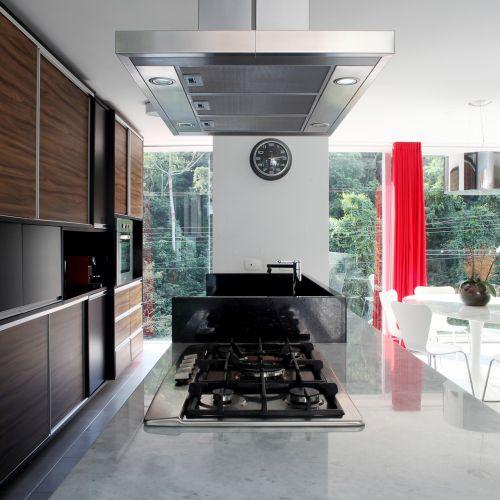 A bancada da cozinha foi executada em mármore branco espírito santo e granito preto são gabriel, enquanto o mobiliário da cozinha foi construído em MDF formicado padrão pau-ferro. A única parede que se interpõe entre a cozinha e as salas é a que envolve a geladeira e o freezer (ao fundo, com o relógio)