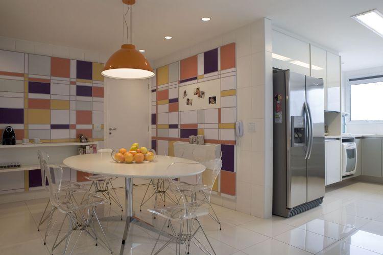 Na copa, mais um trabalho de marcenaria para arrematar e organizar o ambiente. Inspirada nos traços de Piet Mondrian, a arquiteta desenhou os painéis de MDF forrados com película adesiva que, com exceção das cores, remetem ao neoplaticismo. Inesperadamente, surgem das paredes porta-revistas e aparadores. Ao fundo, o ambiente relaciona-se com a cozinha, que tem armários da Ornare