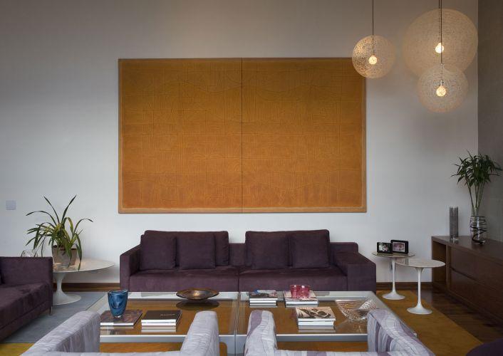 Em contraposição ao branco da parede, a tela em pintura acrílica do artista plástico Rubens Ianelli e os sofás saltam aos olhos. A mesa de centro de vidro e metal é da Brinna; as mesas laterais, modelo Saarinen em três tamanhos, têm tampo de mármore de Carrara