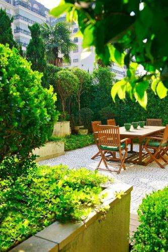 O conjunto de mesa e cadeiras de madeira ambienta o jardim, emoldurado por jardineiras elevadas, construídas para garantir profundidade suficiente o plantio. A vegetação rente ao muro é murta (Murraya paniculata) e os arbustos esculpidos em formato redondo, buxinho (Buxus sempervirens). O piso foi revestido com mosaico português