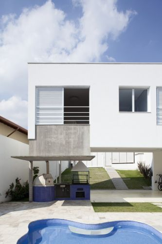 Detalhe da área de lazer da casa na Granja Viana, zona sul de São Paulo, projeto de Gilberto Belleza. A área da churrasqueira e do forno de pizza tem proteção da aba de concreto aparente