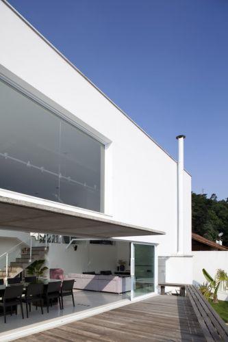 O ambiente de estar e jantar da casa projetada pelo arquiteto Gilberto Belleza é integrado à varanda com deck de madeira e protegida pela aba de concreto aparente.