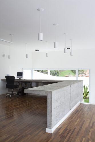 O escritório, com mobiliário de concreto aparente, tem piso de cumaru, material que reveste todo o pavimento superior. Projeto de Gilberto Belleza para uma casa na Granja Viana, zona sul de São Paulo