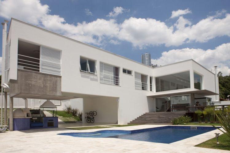Vista lateral da casa projetada pelo arquiteto Gilberto Belleza. Com as amplas aberturas para o exterior, a construção exibe detalhes de concreto aparente e madeira nua que movimentam a fachada