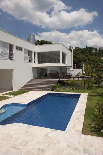 Pedras goiás revestem o piso da área de lazer e contrastam com o verde do jardim da casa projetada pelo arquiteto Gilberto Belleza